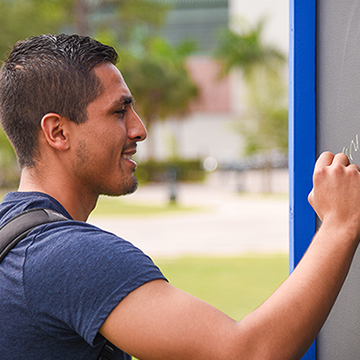FGCU student writing on a chalkboard