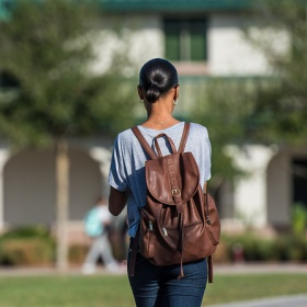 Girl walking on campus with back towards camera