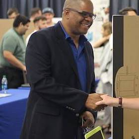 Student shaking investor's hand at Entrepreneurship and Innovation Expo